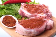 Raw pork chops with herbs and spices on cutting board. Ready for cooking. Royalty Free Stock Photography