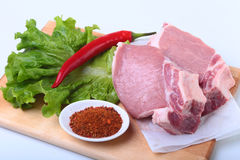 Raw pork chops with herbs and spices on cutting board. Ready for cooking. Raw pork chops with herbs and spices on cutting board. Ready for cooking Royalty Free Stock Image