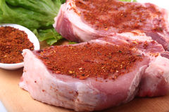 Raw pork chops with herbs and spices on cutting board. Ready for cooking. Raw pork chops with herbs and spices on cutting board. Ready for cooking Royalty Free Stock Photography