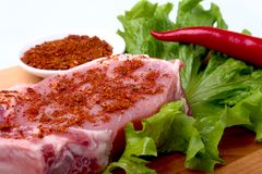 Raw pork chops with herbs and spices on cutting board. Ready for cooking. Stock Images