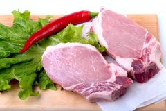 Raw pork chops with herbs and spices on cutting board. Ready for cooking. Stock Photography