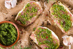 Raw pork chops marinated with pesto sauce.  Stock Photography