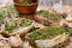 Raw pork chops marinated with pesto sauce.  Stock Photo