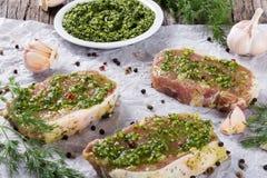 Raw pork chops marinated with pesto sauce Royalty Free Stock Photos