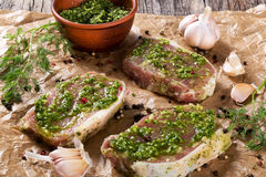 Raw pork chops marinated with pesto sauce.  Royalty Free Stock Images