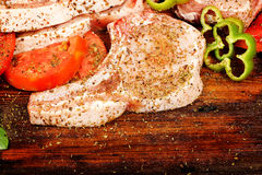 Raw pork chops. With other ingredients on wood Royalty Free Stock Photo