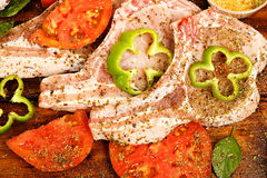Raw pork chops. With other ingredients on wood Royalty Free Stock Images