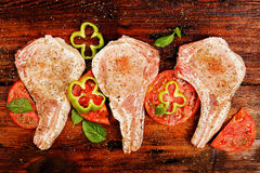 Raw pork chops. With other ingredients on wood Stock Image