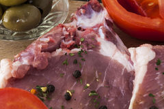Raw pork chops pepper olives and tomatoes Royalty Free Stock Photos