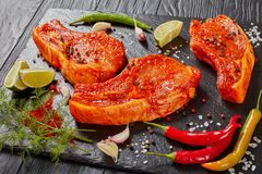 Raw pork chops prepared to roast. Raw pork chops prepared to cook, marinated with spices and red sriracha sauce on black slate tray with chili pepper, salt, lime Stock Photography