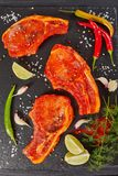 Raw pork chops prepared to cook. Marinated with spices and red sriracha sauce on black slate tray with chili pepper, salt, lime slices and spices, vertical Stock Photography