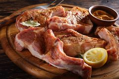 Raw pork chops on round board. Raw pork chops on bone seasoned with spices, peppercorns and bay leaf on a round cutting wooden board on wooden rustic table, view Stock Photos