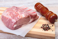 Raw pork chops and spice grinder on cutting board. Ready for cooking. Royalty Free Stock Photos