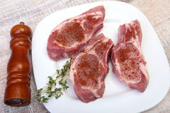 Raw pork chops and spice grinder on cutting board. Ready for cooking. Stock Image