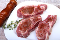 Raw pork chops and spice grinder on cutting board. Ready for cooking. Royalty Free Stock Image