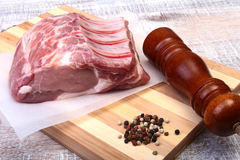 Raw pork chops and spice grinder on cutting board. Ready for cooking. Royalty Free Stock Photography