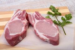 Raw pork chops, spices and basil on cutting board. Ready for cooking. Raw pork chops, spices and basil on cutting board. Ready for cooking Royalty Free Stock Images