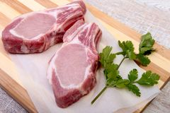 Raw pork chops, spices and basil on cutting board. Ready for cooking. Stock Photos