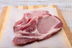 Raw pork chops, spices on cutting board. Ready for cooking. Raw pork chops, spices on cutting board. Ready for cooking Stock Images