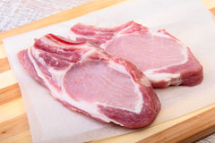 Raw pork chops, spices on cutting board. Ready for cooking. Stock Images