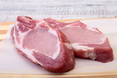 Raw pork chops, spices on cutting board. Ready for cooking. Stock Photo
