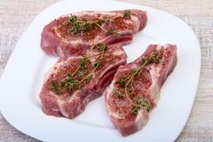 Raw pork chops, spices and rosemary on cutting board. Ready for cooking. Raw pork chops, spices and rosemary on cutting board. Ready for cooking Royalty Free Stock Photos