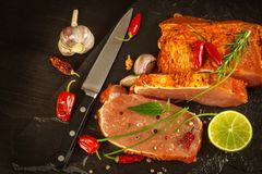 Raw pork chops with spices. Sliced meat prepared on the grill. Stock Photos