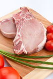 Raw pork chops with vegetables on chopping board Royalty Free Stock Photos