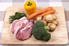 Raw pork chops and vegetables Stock Photos