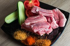 Raw pork chops with vegetables and spices on a. Plate Stock Photography
