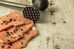 Raw pork chops on a wooden table. Three raw, broken chops sprinkled with peppercorns and salt crystals, meat tenderizer on an old wooden kitchen table. Close Royalty Free Stock Images