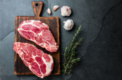 Raw pork cutlet chop for grill BBQ with herbs on wooden board, slate background, top view, copy spaces.  stock photo