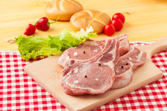 Raw Pork Cutlet Chops. High Angle View of Raw Pork Cutlet Chops Seasoned with Salt, Pepper and Fresh Herbs on Clean Wooden Board on Light Textured Surface Stock Images