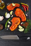 Raw pork cutlets prepared to roast. Marinated with spices and red sriracha sauce on black slate tray with chili pepper, salt, lime slices and spices on wooden Royalty Free Stock Photography
