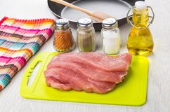 Raw pork on cutting board, frying pan, vegetable oil, salt, pepp Royalty Free Stock Photo