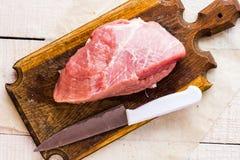 Raw pork on a cutting board, knife Stock Photo