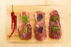 Raw pork on cutting Board with spices and herbs Stock Photos