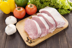 Raw pork on cutting board and vegetables. Stock Photo
