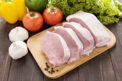 Raw pork on cutting board and vegetables. Raw pork on cutting board and vegetables Stock Photo