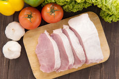 Raw pork on cutting board and vegetables. Royalty Free Stock Images