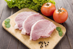 Raw pork on cutting board and vegetables. Royalty Free Stock Photo