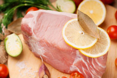 Raw pork on cutting board and vegetables. On a cutting board Stock Image