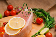 Raw pork on cutting board and vegetables. On a canvas textile background Stock Image