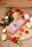 Raw pork on cutting board and vegetables. On a canvas textile background Royalty Free Stock Images
