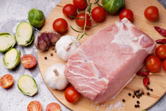 Raw pork on cutting board and vegetables. Raw pork on cutting board and colorful vegetables Royalty Free Stock Photography