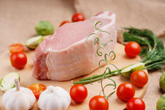 Raw pork on cutting board and vegetables. Raw pork on cutting board and colorful vegetables Stock Images