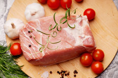 Raw pork on cutting board and vegetables. Raw pork on cutting board and colorful vegetables Royalty Free Stock Image