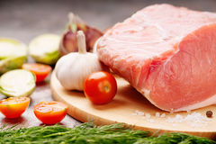 Raw pork on cutting board and vegetables. Raw pork on cutting board and colorful vegetables Stock Photo