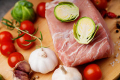 Raw pork on cutting board and vegetables. Raw pork on cutting board and colorful vegetables Royalty Free Stock Images