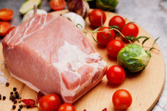 Raw pork on cutting board and vegetables. Raw pork on cutting board and colorful vegetables Stock Photography